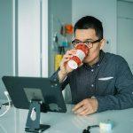 Man drinkt koffie achter computerscherm